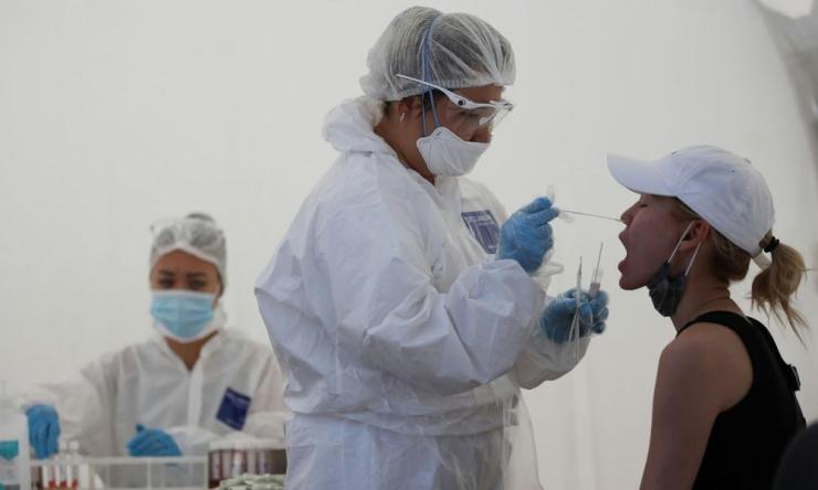 A health worker takes a swab from a woman at a mobile testing station for coronavirus in Almaty, Kazakhstan