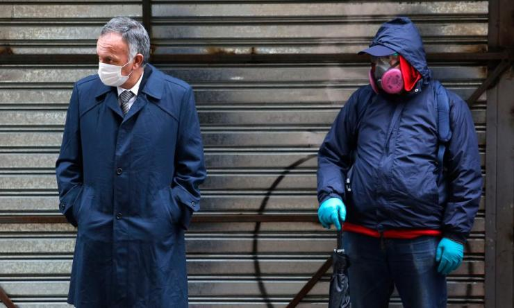 People wearing masks line up to collect state bonds or loans to face the economic crisis caused by the coronavirus pandemic on July 8, 2020 in Santiago, Chile.