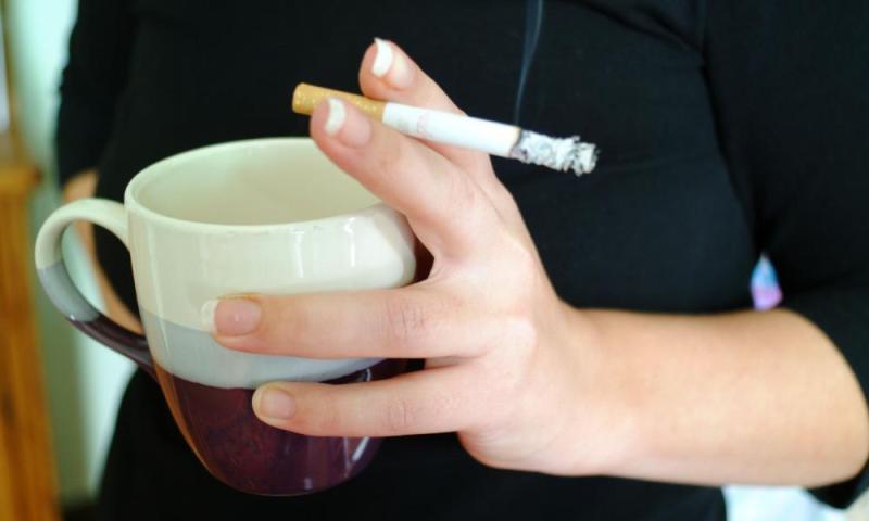 woman holding cigarette and mug