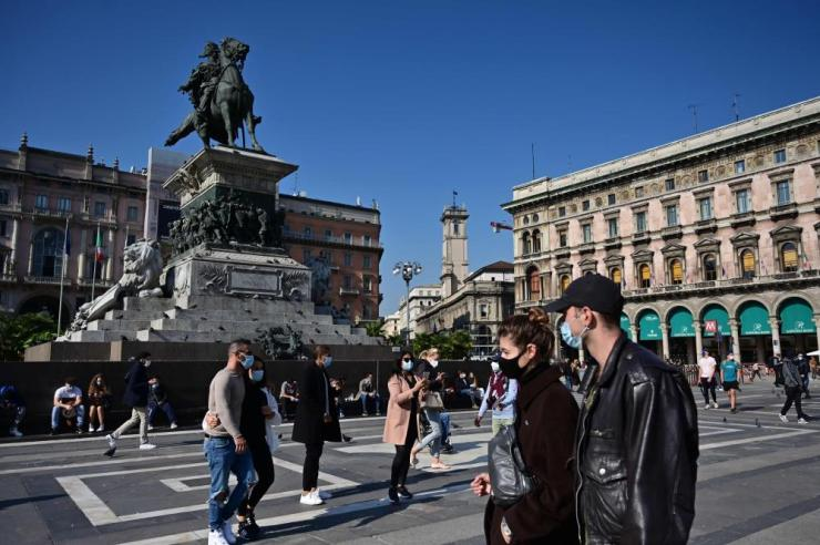 People wearing protective masks walk across the Piazza del Duomo in Milan.