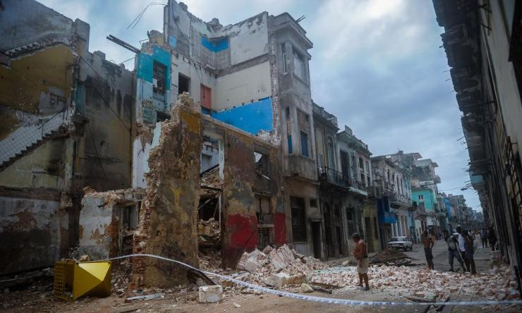 Cubans stand by a collapsed building in Havana.
