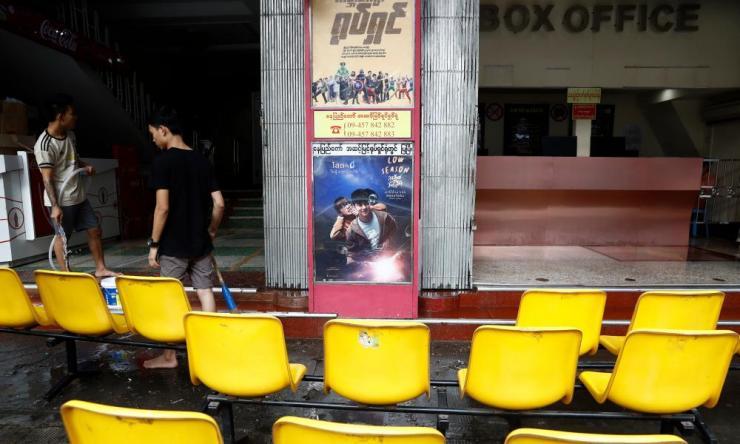 Men clean a closed cinema in Yangon, Myanmar, 16 March 2020.