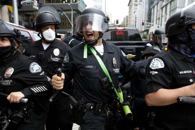 A police officer yells to protesters to back up during a demonstration over the death of George Floyd, Friday, May 29, 2020, in Los Angeles. Floyd died in police custody on Memorial Day in Minneapolis. (AP Photo/Jae C. Hong)