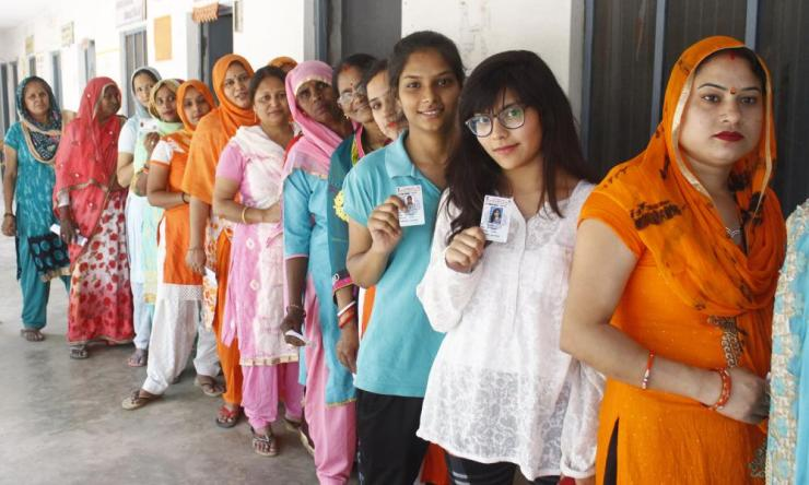 Voters wait outside a polling station in Gurugram.