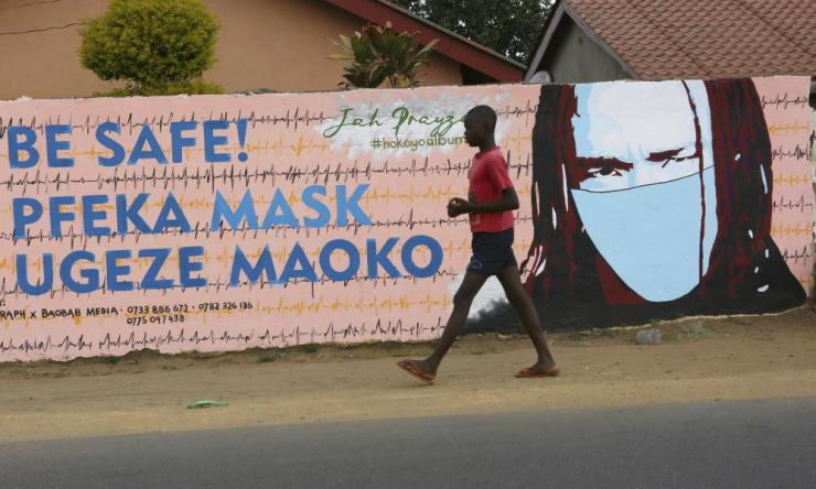 A young boy walks past a mural in Harare urging people to wear face masks.