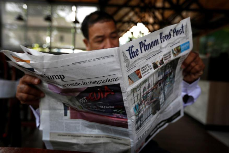 a man reading the phnom penh post in cambodia in may 2018