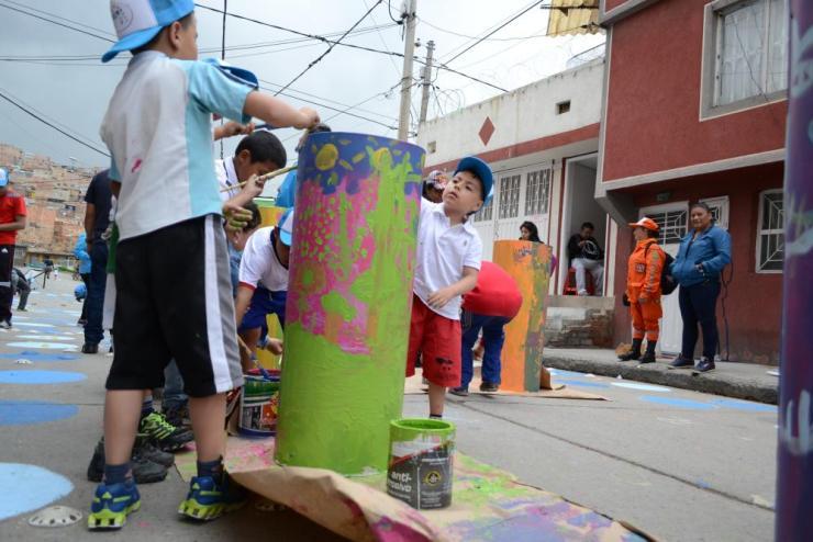Children help brighten up a street in Bogotá