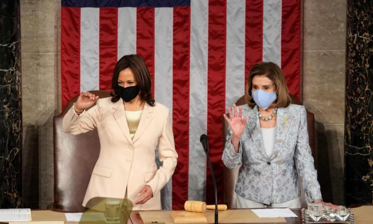 Nancy Pelosi and Kamala Harris wave to colleagues while they wait for Joe Biden to arrive