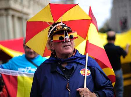 An anti-independentist Catalan wearing glasses and an umbrella hat bearing colours of the Spanish flag takes part in a demonstration for the unity of Spain at Catalunya square in Barcelona on October 12, 2013 ( Josep Lago (AFP) )