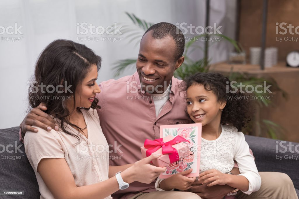 African American Daughter And Husband Presenting Gifts To