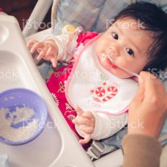 Baby Girl Chair Covers Hire Cost Eurasian Sitting In High While Being Fed Stock Photo Image