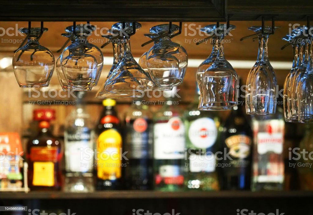 bar counter glasses hanging over a bar rack many colorful of liquor bottles on the shelf stock photo download image now istock