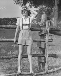 Barefoot Woman In Shorts Standing Wooden Fence