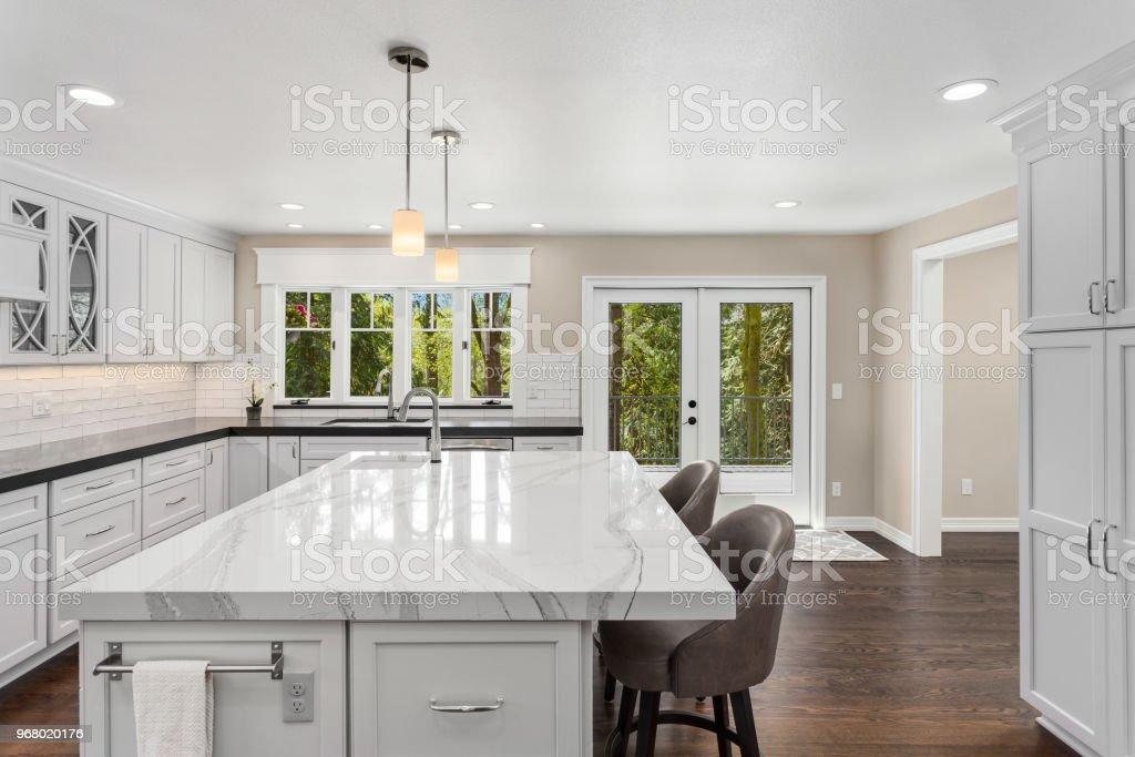 kitchen island with range new countertops 在新豪宅與島吊燈烤箱範圍和硬木地板的美麗廚房照片檔及更多不銹鋼照片 在新豪宅與島 吊燈 烤箱 範圍和硬木地板的美麗