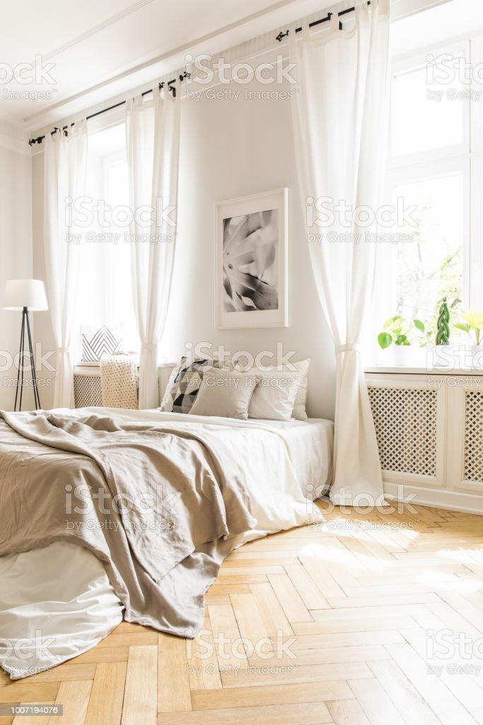 photo libre de droit de couverture beige sur le lit et affiche a linterieur de la chambre blanche avec rideaux aux fenetres vraie photo banque d images et plus d images libres de droit