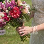 Bride In Lace Wedding Dress Holding A Vibrant Bouquet Pink White Green Purple And Fuchsia Floral Arrangement With Anemones And Dahlias In The Hands Of A Young Bride Stock Photo Download