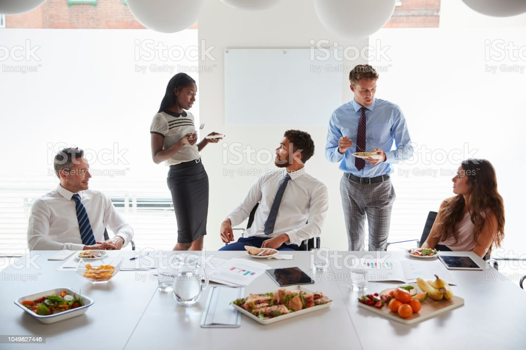 Businessmen And Businesswomen Meeting In Modern Boardroom Over Working Lunch Stock Photo - Download Image Now - iStock