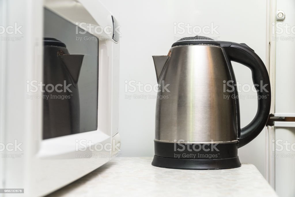 https www istockphoto com photo electric kettle and microwave on the kitchen table gm968232678 264015999
