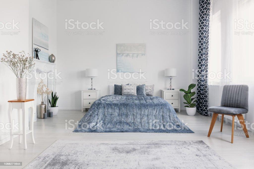photo libre de droit de chaise grise a cote de lit bleu a linterieur de la