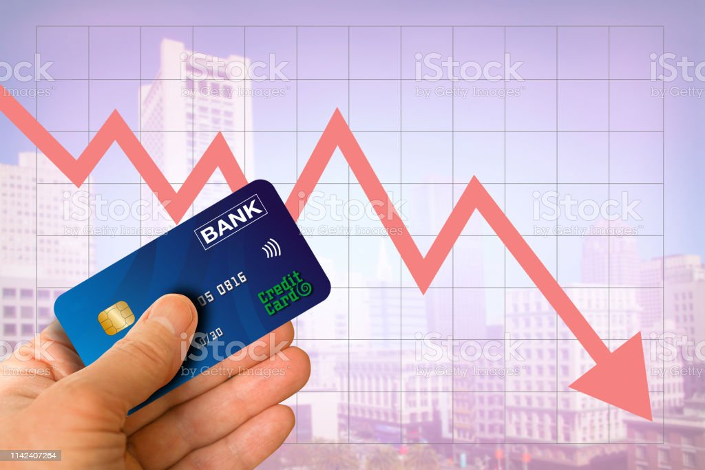 Hand Holding Credit Card From Bank With Cityscape And Red Arrow Going Down Showing Real Estate Market Economy Going Down With Blurred Office Buildings In The Background Stock Photo Download Image