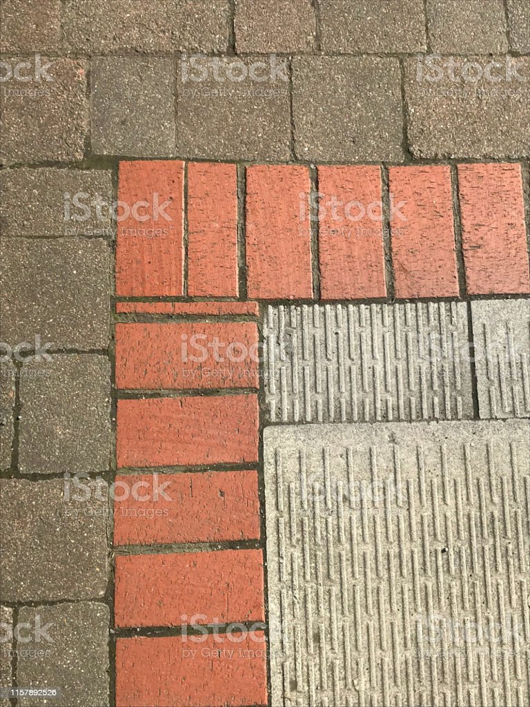 image of block paving corner with grey ridged concrete patio slabs red brick edging and brown grey blocks hardscaping by builders for front garden driveway drive for cars to park parking outside