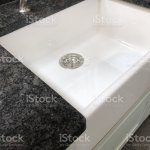 Image Of White Ceramic China Butler Belfast Kitchen Sink With White And Grey Granite Marble Worktop Countertop Integrated Granite Draining Board With Grooves Runnels And Drains Shining Concealed Under Wall Cabinet Lights