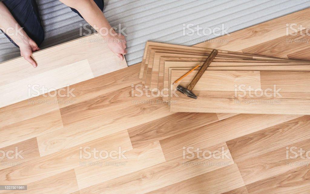 https www istockphoto com photo installing laminated floor detail on man hands holding wooden tile over white foam gm1227321961 361926232