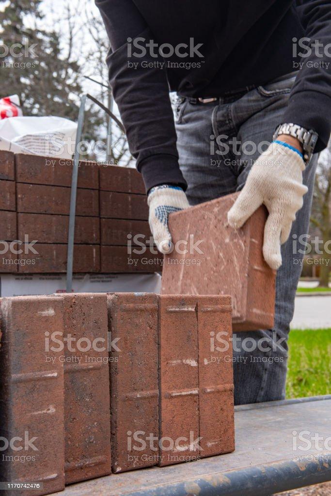 instalacion de ladrillos de pavimentadora para patio en patio trasero manos enguantadas de un obrero cargando ladrillos a dos ruedas foto de stock y mas banco de imagenes de acera istock