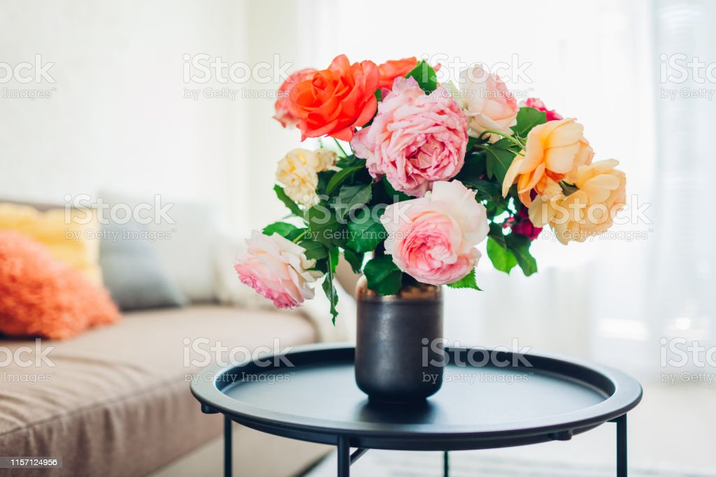 interior of living room decorated with flowers on coffee table and cozy couch with cushions fresh roses stock photo download image now istock