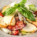 Italian Cuisine Classic Caesar Salad With Chicken Cherry Tomatoes Mix Salad Parmesan Cheese Bread Croutons Rusks And Basil The Concept Is A Beautiful Serve In The Restaurant Copy Space Stock Photo