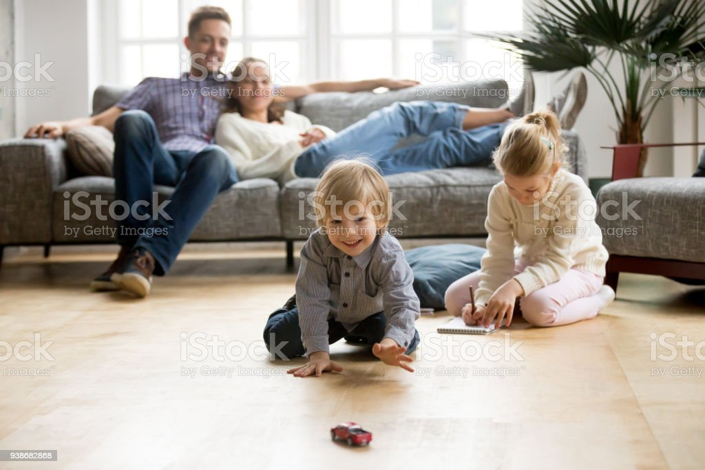 Kids Playing On Floor Parents Relaxing On Sofa At Home