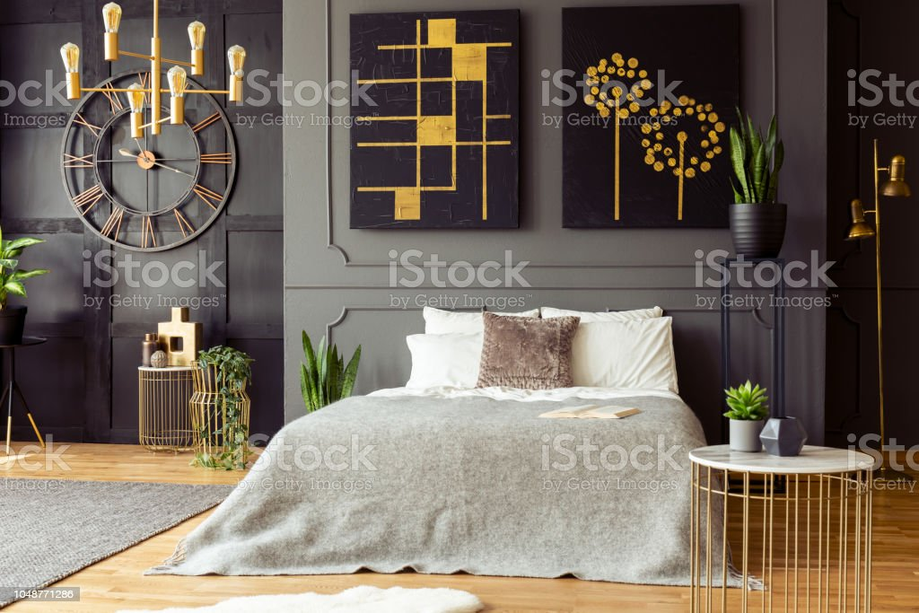 kingsize bed with bright sheets standing in real photo of dark bedroom interior with gold lamps fresh plants simple paintings and wainscoting on wall stock photo download image now istock