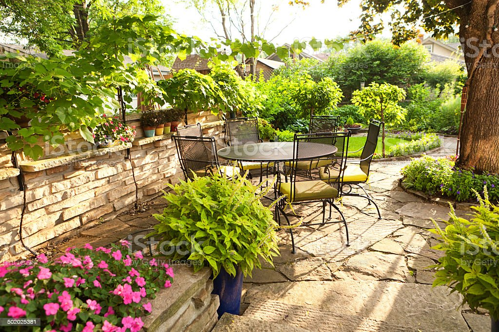 https www istockphoto com photo landscaped back yard patio garden with potted plants furniture flowers gm502025381 43769658