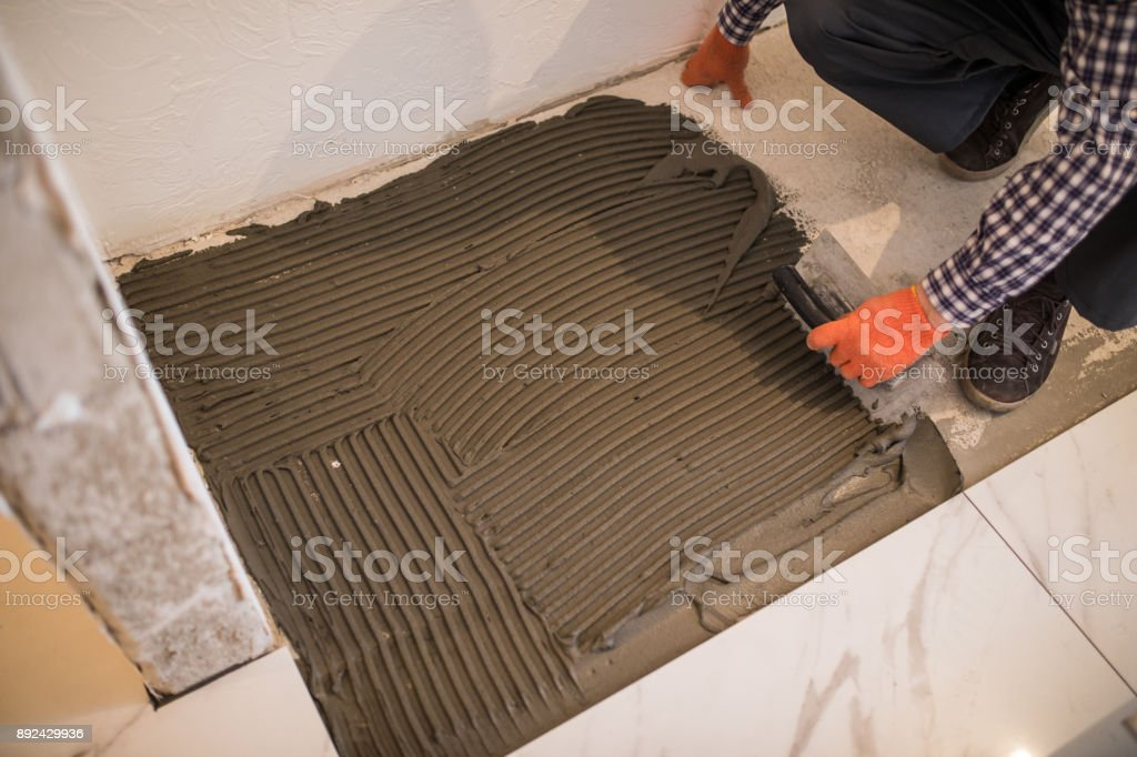 https www istockphoto com photo laying ceramic tiles troweling mortar onto a concrete floor in preparation for laying gm892429936 247005305