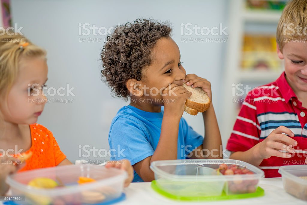 Little Boy Eating His Lunch At School Stock Photo - Download Image Now - iStock