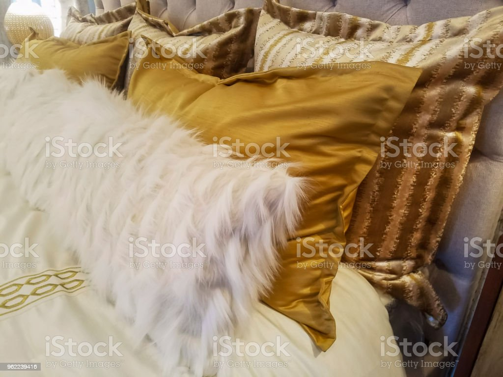 luxiourous gold and fur pillow shams on bed propped against quilted beadstead stock photo download image now istock