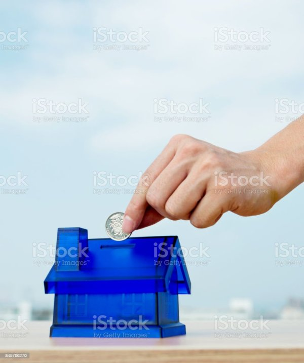 Man Hand Putting Coin In House Shaped Piggy Bank Stock