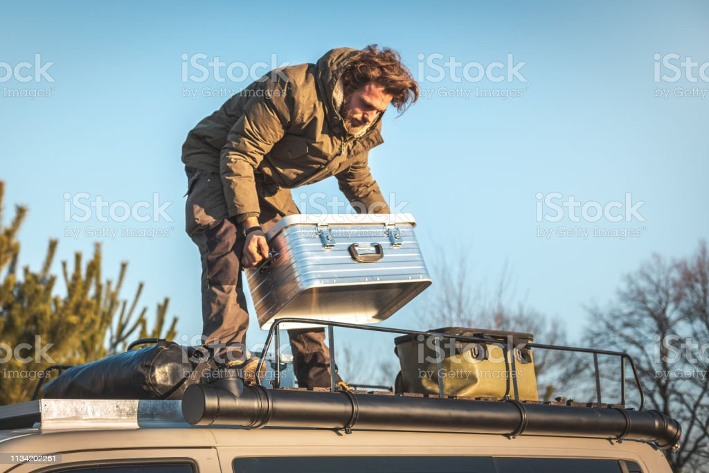 a man is lifting a metal box from the roof rack of a van stock photo download image now istock