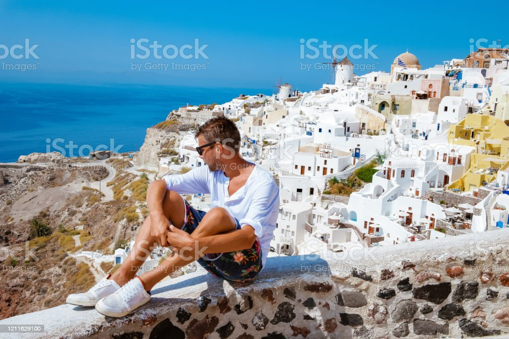 Man On Vacation Greece Visisting Oia Santorini Guy On Holiday In Greece On A Luxury Trip To Oia Whitewashed Village With Greek Churches Stock Photo Download Image Now Istock