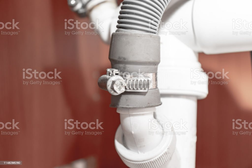 metal clamp for connection of dishwasher drain hose under kitchen sink close up stock photo download image now istock