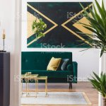 Modern And Luxury Interior Of Living Room With Pomegranate Shelf Gold Coffee Table Velvet Sofa Tropical Plant And Elegant Accessories Design Paintings On The Wall Stylish Home Decor Template Stock Photo