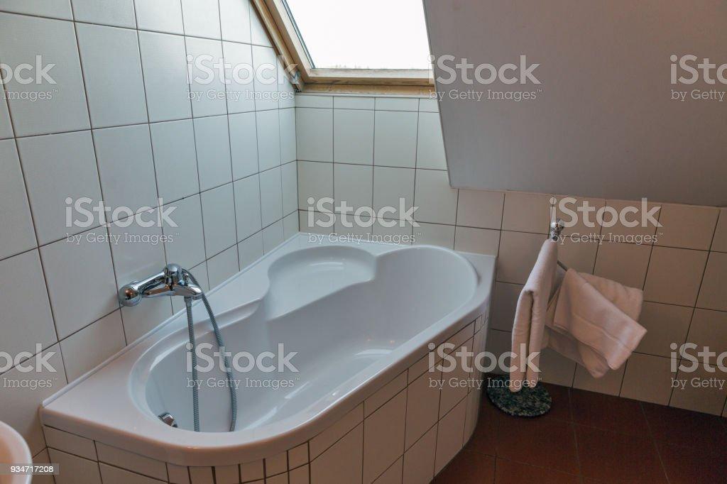 https www istockphoto com fr photo salle de bains moderne avec baignoire dangle et de la fen c3 aatre gm934717208 255870977