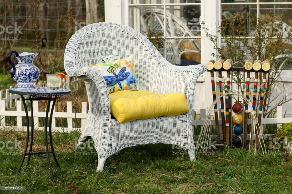 outdoor scene with a beautiful black cat sitting on a white wicker chair with a yellow cushion next to a table with a drink and a blue pitcher stock photo download
