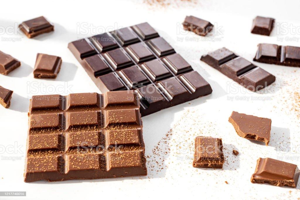 https www istockphoto com fr photo morceaux de chocolat noir et lait avec de la poudre de cacao sont dispers c3 a9s sur un gm1217740014 355573143