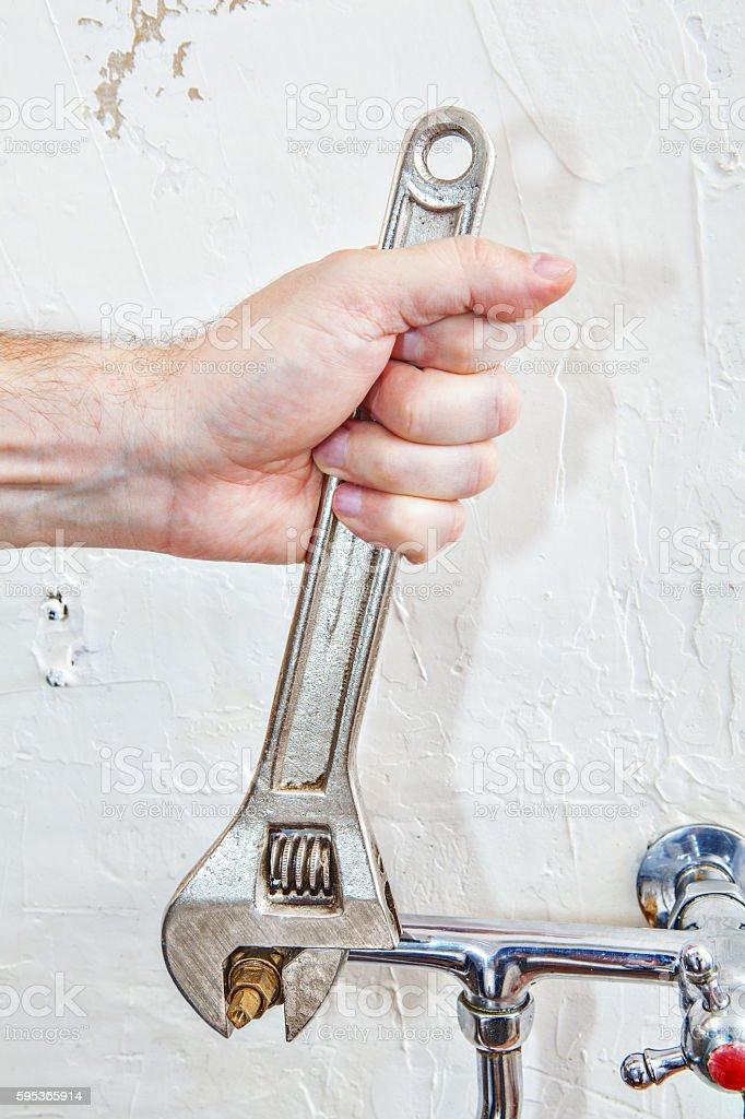 https www istockphoto com photo plumber hands fixing water tap valve with plumbing adjustable spanner gm595365914 102105677