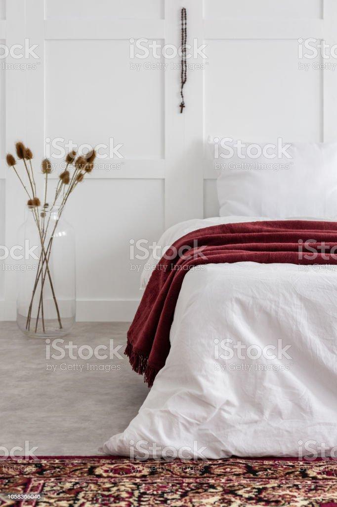 https www istockphoto com fr photo chapelet en bois rouge accroch c3 a9 au mur de blanc un minimum chambre avec lit gm1058365046 282857047