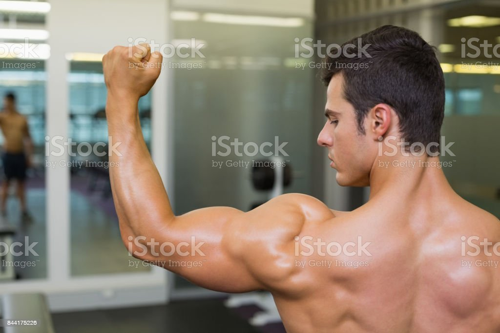 shirtless muscular man flexing