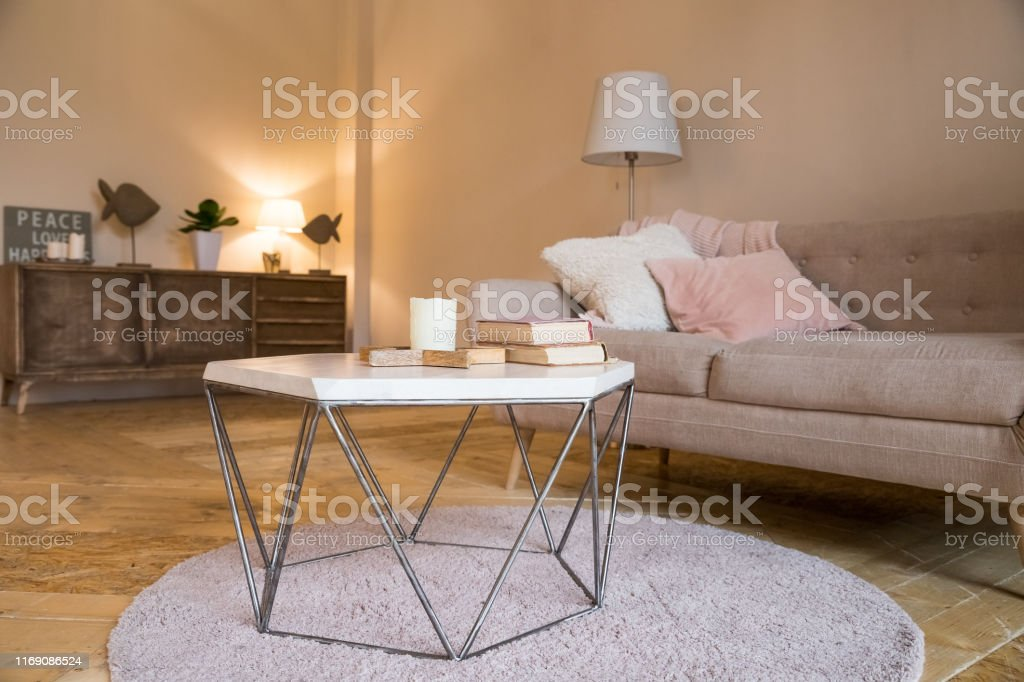 https www istockphoto com photo small coffee table and candles next to designed sofa with pastel colored pillows gm1169086524 323031359