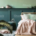 Stylish Interior Design Of Bedroom With Modern Furnitures Plants And Elegant Accessories Shelf Above The Bed Beautiful Pink And Green Bed Sheets Blankets And Pillows Modern Home Decor Template Stock Photo