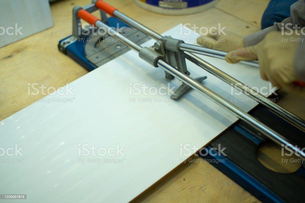 https www istockphoto com photo tile cutter builder tiler working with floor tile cutting equipment gm1220037815 357080457